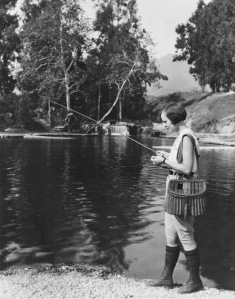 Young woman with bobbed hair fishing on a pebbled shore.