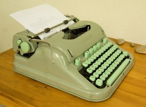Pale green Hermes typewriter on wooden desk.